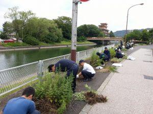 瀬田川沿いの歩道を清掃している写真です。約10名の社員が写っています。